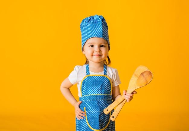 Bonne petite fille en costume de chef tenant des cuillères en bois sur une surface jaune avec un espace pour le texte