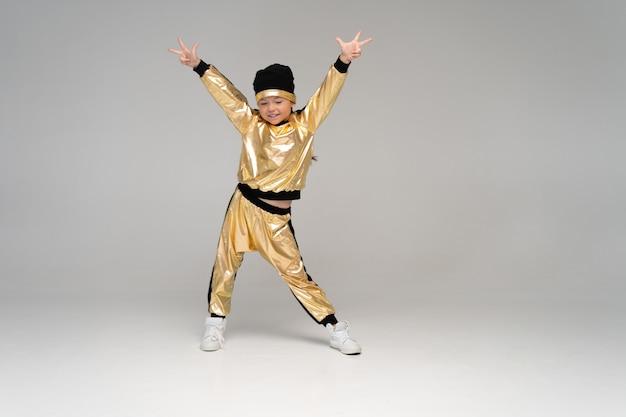 Bonne petite fille en costume d'or dansant isolé sur une surface blanche