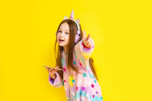Bonne petite fille dans une licorne kigurumi sur fond jaune