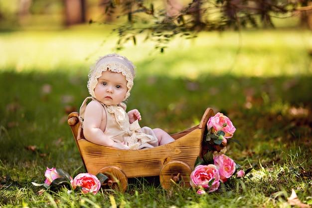Bonne petite fille dans un panier avec des fleurs roses à l'extérieur en été.