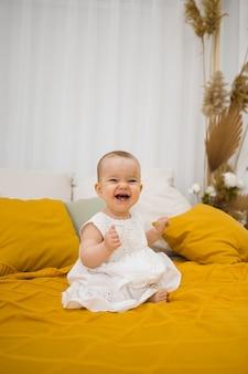 Bonne petite fille dans une robe blanche est assise sur une couverture jaune sur le lit dans la chambre