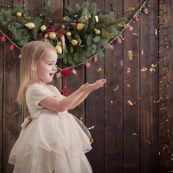 Bonne petite fille avec des décorations de noël sur bois foncé