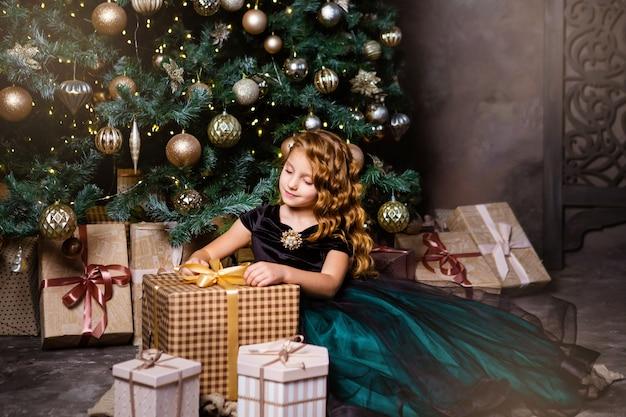 Bonne petite fille déguisée assise près de l'arbre de noël avec la boîte présente. temps de noël et concept de nouvel an. couleurs vertes et dorées des décorations.