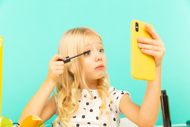 Bonne petite fille devant la caméra du téléphone faisant de la vidéo pour vlog. travailler en tant que blogueur, enregistrer un didacticiel vidéo pour internet.