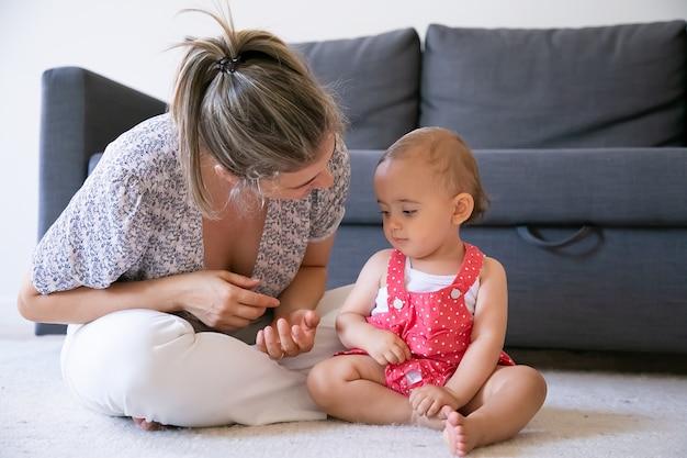 Bonne petite fille écoute maman et assise sur un tapis pieds nus. mère blonde assise les jambes croisées et parle à sa fille. beau bébé sérieux regardant les mains de maman. concept de week-end et maternité