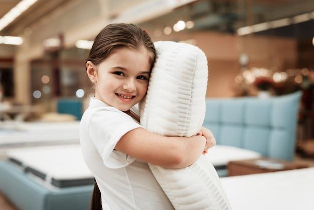Bonne petite fille étreignant oreiller dans un magasin de matelas
