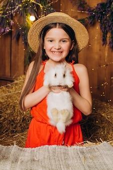 Bonne petite fille à la ferme tient un lapin blanc dans ses bras par le foin de pâques et le concept de l'enfance heureuse