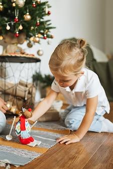 Bonne petite fille jouant sur le mur d'un arbre de noël avec un cerf jouet dans la chambre. joyeux noël et bonne année concept. espace pour le texte. moments chaleureux en famille.