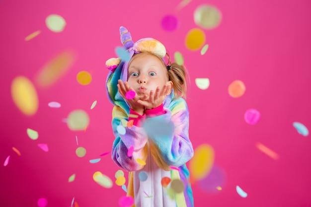 Bonne petite fille en licorne kigurumi sur un mur rose se réjouit de confettis multicolores