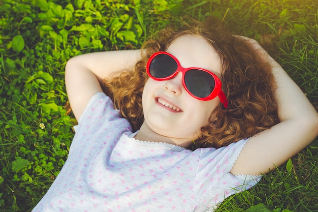 Bonne petite fille avec des lunettes, allongé sur l'herbe dans un parc d'été. concept d'enfance heureuse.