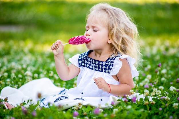 Bonne petite fille mangeant un morceau de bonbon sur un bâton en forme de coeur. concept de la saint-valentin