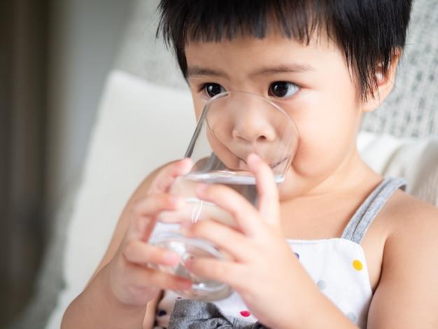 Bonne petite fille mignonne tenant un verre et de l'eau potable.