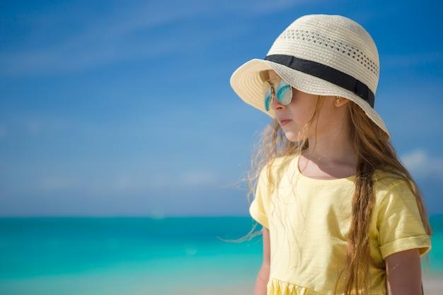 Bonne petite fille sur la plage pendant les vacances d'été