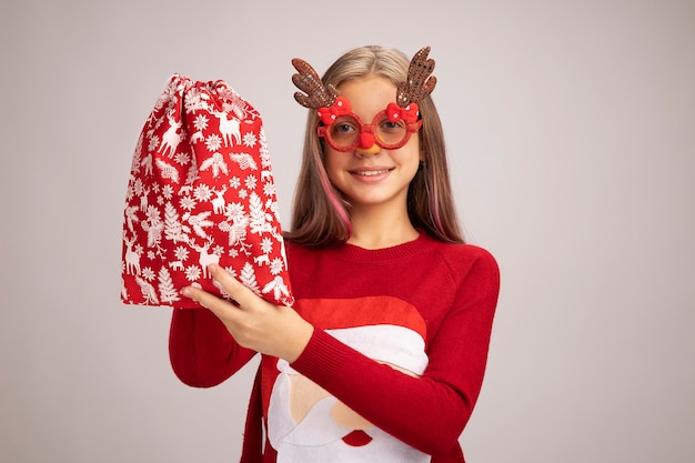 Bonne petite fille en pull de noël portant des lunettes de fête drôles tenant un sac rouge santa avec des cadeaux regardant la caméra souriant joyeusement debout sur fond blanc