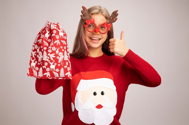 Bonne petite fille en pull de noël portant des lunettes de fête drôles tenant un sac rouge santa avec des cadeaux regardant la caméra souriant joyeusement montrant les pouces vers le haut debout sur fond blanc