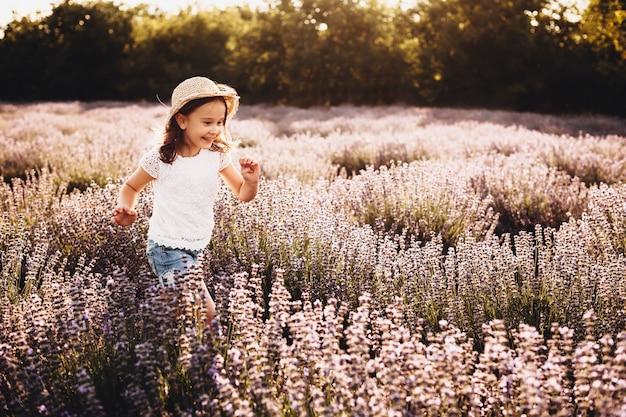 Bonne petite fille qui court dans un champ de fleurs contre le coucher du soleil. charmant enfant riant en jouant à l'extérieur.