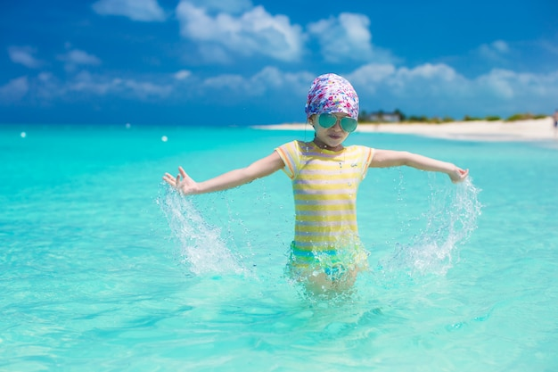 Bonne petite fille s'amuser à la plage pendant des vacances des caraïbes
