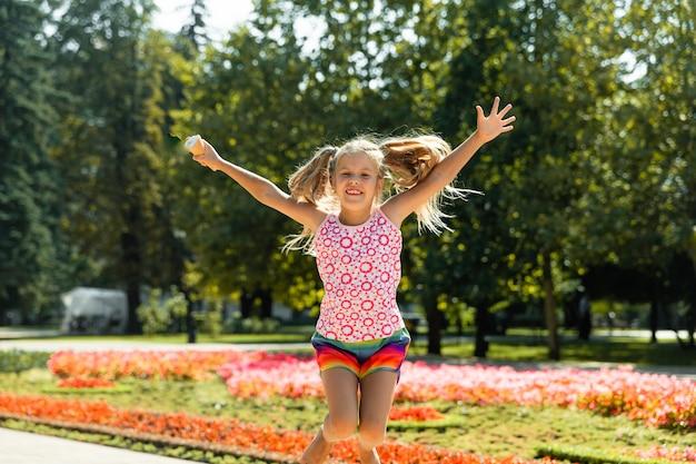 Bonne petite fille sautant dans le parc. petite fille mangeant des glaces et s'amusant dans la ville.