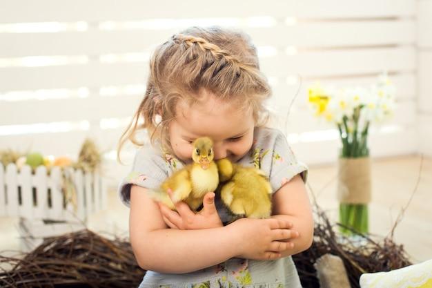 Bonne petite fille se joue avec de jolis canetons de pâques moelleux.