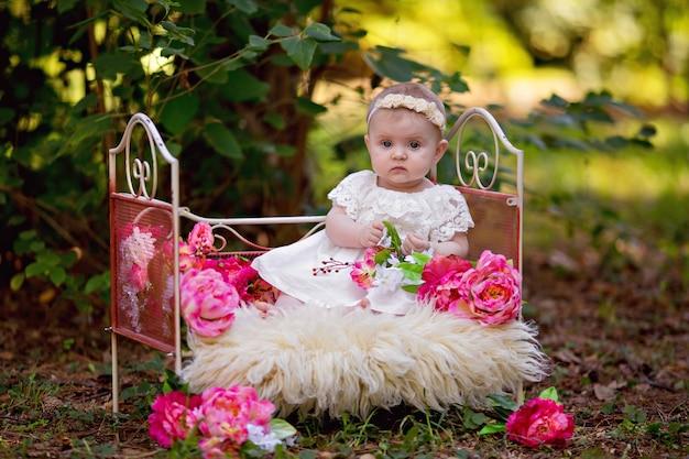 Bonne petite princesse bébé fille au lit avec des fleurs roses à l'extérieur en été.