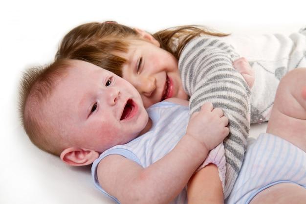 Bonne petite soeur étreignant son frère couché