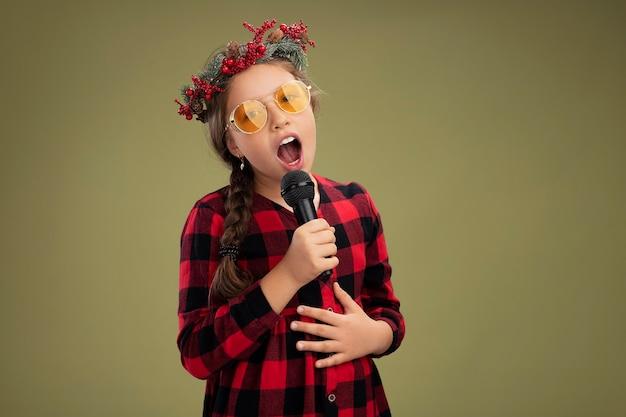 Bonne et positive petite fille portant une couronne de noël en robe à carreaux tenant le chant microphone debout sur fond vert