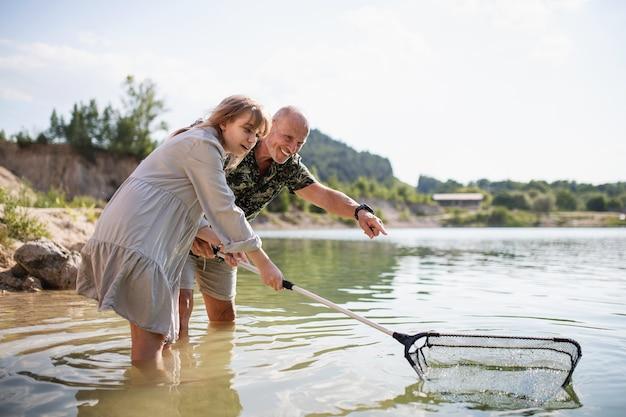 Bonne préadolescente et grand-père avec filet de pêche en vacances d'été au bord du lac.