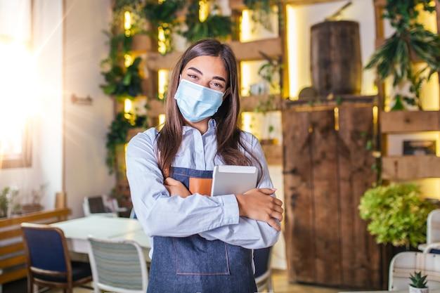 Bonne serveuse féminine à l'aide de tablette numérique tout en portant un masque protecteur au restaurant ou au café. ouvrir à nouveau après le verrouillage en raison de l'épidémie de coronavirus covid-19, nouvelle normale