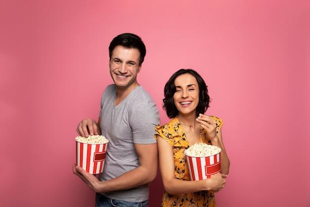 Bonne soirée. couple heureux, qui sourient et regardent la caméra tout en mangeant du pop-corn.