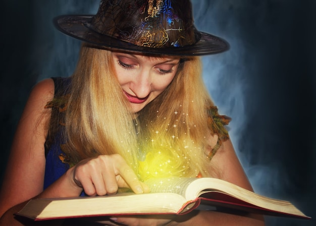 Une bonne sorcière au chapeau lit des sorts magiques dans le livre sur fond de brouillard.