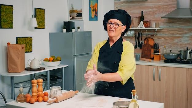 Bonne vieille femme de boulanger frappant des mains avec de la farine à la caméra. cuisinier professionnel applaudit et mouche à poudre, chef à la retraite saupoudrant d'ingrédients sur la pâte préparant du pain traditionnel.