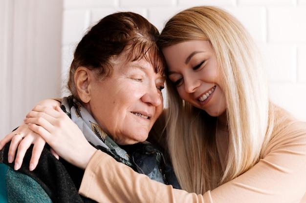 Bonne vieille grand-mère étreignant petit-enfant souriant