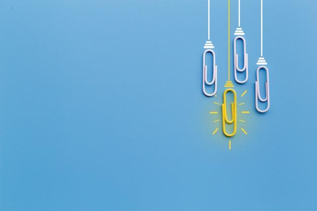 Bonnes idées avec un trombone, pensée, créativité, ampoule sur fond bleu, nouvelles idées