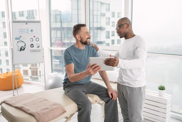 Bonnes perspectives. enthousiaste bel homme regardant son médecin et lui souriant