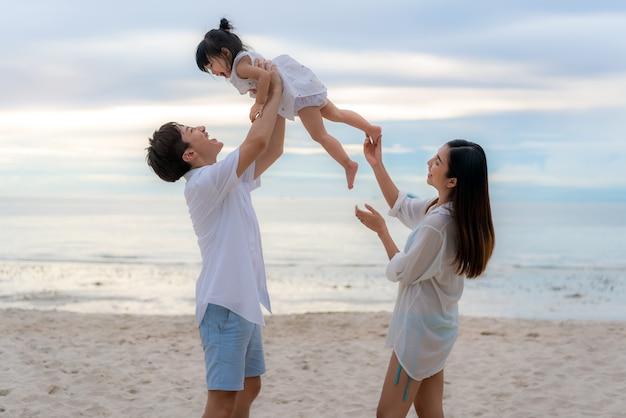 Bonnes vacances en famille au cours de joyeux père, mère et fille marchant et élevant sa fille