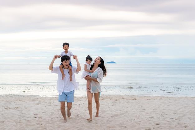 Bonnes vacances en famille pendant joyeux père, mère, fils et fille marchant ensemble