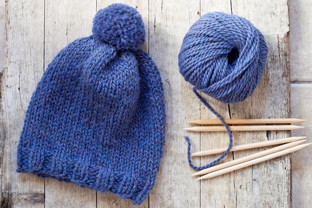 Bonnet bleu en laine, aiguilles à tricoter et fil