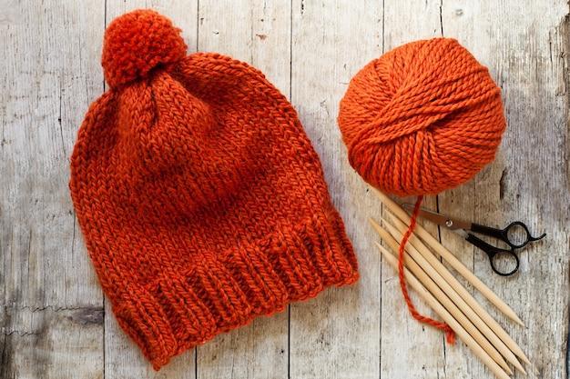 Bonnet en laine orange, aiguilles à tricoter et fil