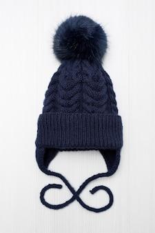 Bonnet en laine tricoté pour enfants avec un pompon, sur fond blanc