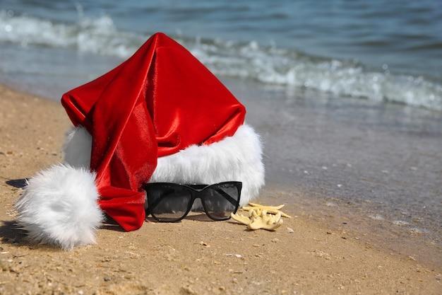 Bonnet de noel avec étoiles de mer et lunettes de soleil sur la plage