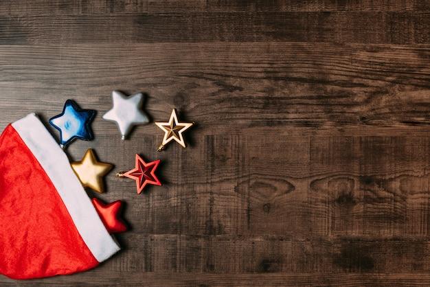 Bonnet de noel avec des étoiles métalliques sur fond en bois. appartement poser pour noël et bonne nouvelle