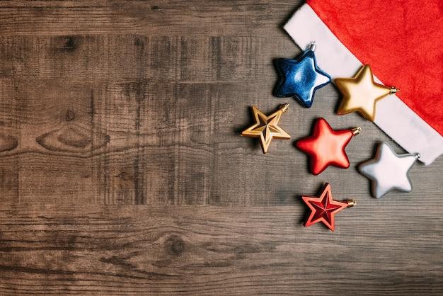 Bonnet de noel avec des étoiles métalliques sur fond en bois.