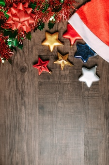 Bonnet de noel avec étoiles métalliques, ornement et ruban rouge sur fond en bois.