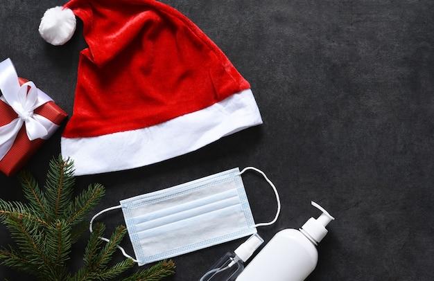 Bonnet de noel, masque médical et antiseptique sur fond de béton noir.