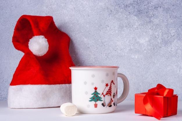 Bonnet de noel, mug au cacao avec des guimauves, cadeau avec ruban rouge