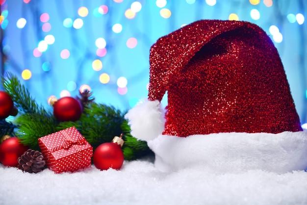 Bonnet de noel sur la neige sur fond de lumières