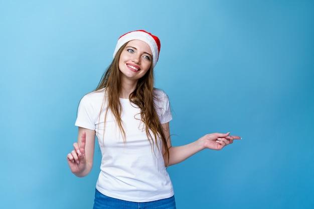 Bonnet de noel de noël portrait de femme isolée souriante fille heureuse sur fond bleu en t-shirt blanc pour...