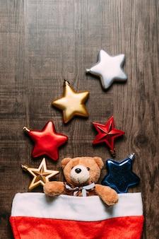 Bonnet de noel avec ours en peluche à l'intérieur et étoiles métalliques sur fond en bois.