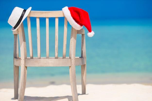 Bonnet de noel rouge et chapeau de paille blanche sur une chaise de plage en vacances tropicales