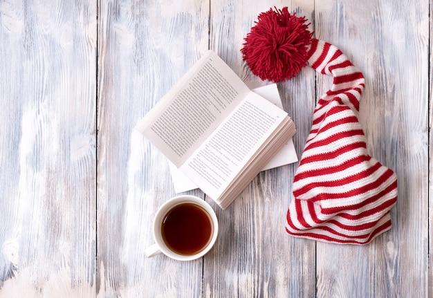 Un bonnet rayé rouge et blanc avec un grand pompon rouge est sur une table en bois avec des livres et une tasse de thé, espace copie, vue de dessus.